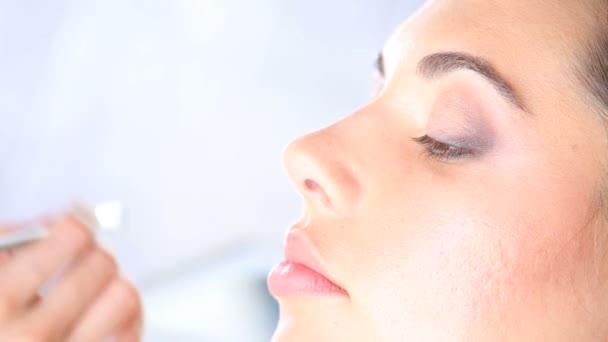 makeup artist applying eyeshadow on eyelid using makeup brush