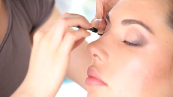 makeup artist applying mascara on eye lashes of model, close up