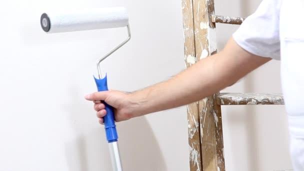 Malermann bei der Arbeit, mit Rollenfarbe an der Wand