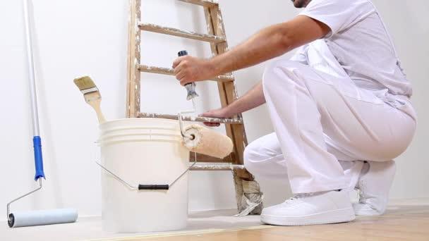 Malermeister bei der Arbeit mit Rolle, Eimer und Leiter