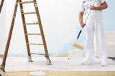 Malermann bei der Arbeit holt Farbe mit Farbroller aus Eimer