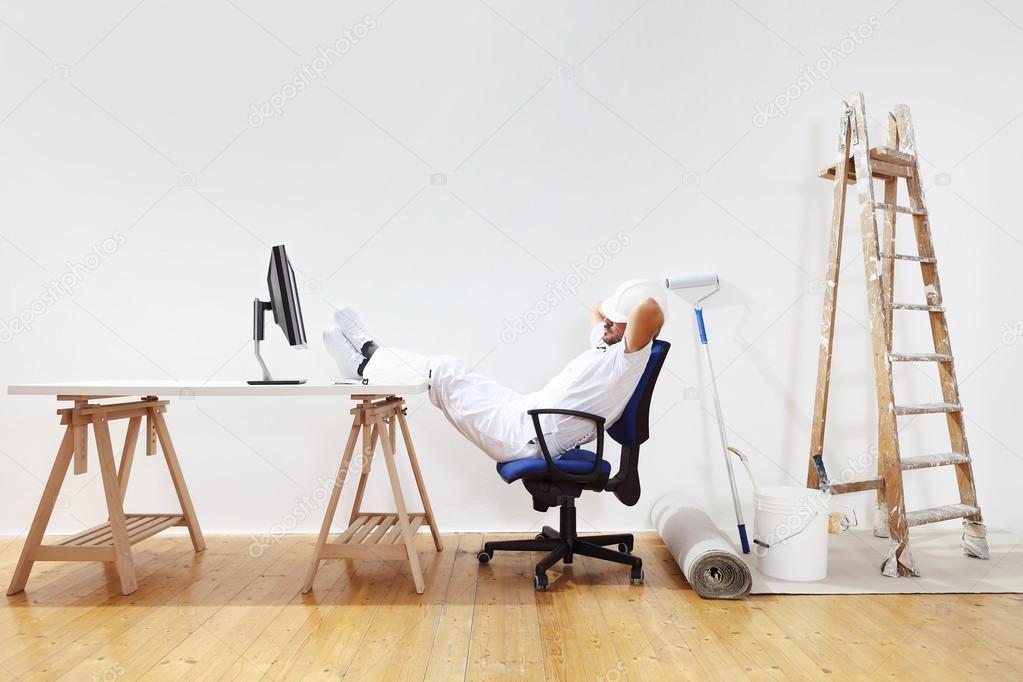 Maler bei der arbeit  Maler-Mann nach der Arbeit mit Füßen auf dem Schreibtisch ...