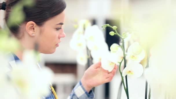 žena v zahradě květů, se dotýká a vůní orchideí