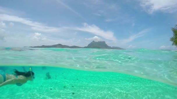 Female diver snorkeling underwater at famous Bora Bora mountain island