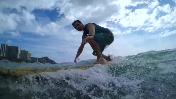 SLOW MOTION: Young man learning to surf at famous surf spot in Waikiki beach