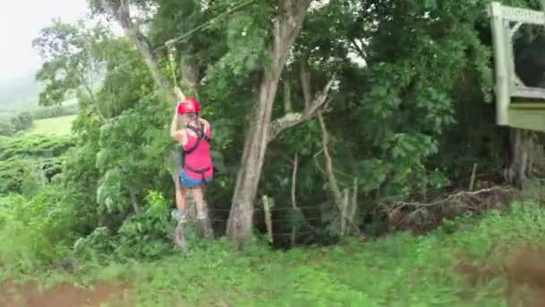 Young smiling girl sliding on cable high above lush jungle rainforest canopies