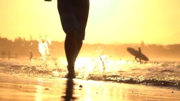Zblízka: Aktivní muž běží v mělkém oceánu vody v ohromující oranžový západ slunce