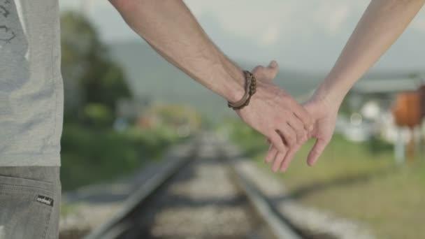 pár drží za ruce a chůzi