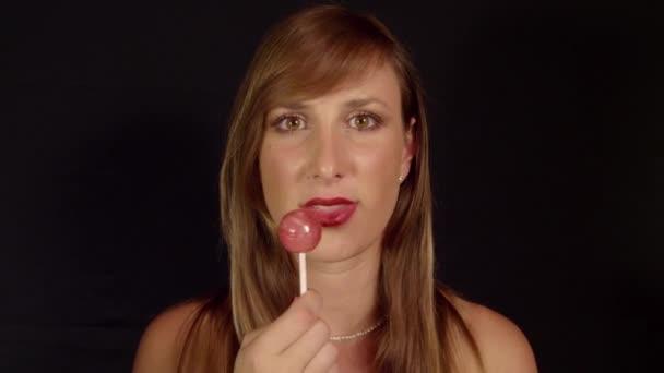 Woman licking lollipop