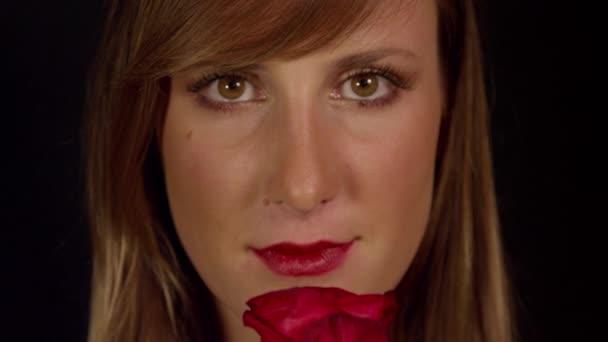 Žena voní červenou růži a úsměvy