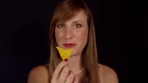 Žena jí tortilla chipsy