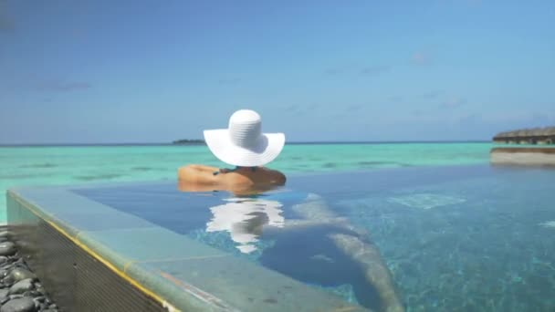 Woman with sun hat relaxing in ocean pool