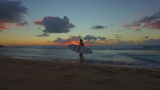 Surfer woman walking on the beach after surfing at sunset