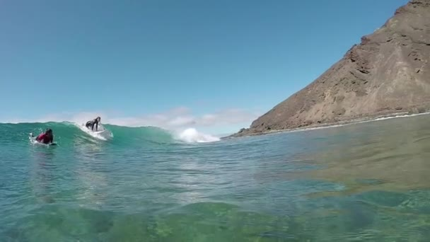 SLOW MOTION UNDERWATER: Surfer girl surfing pass the camera