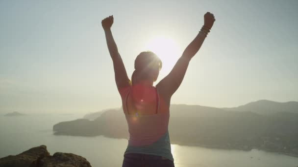 Woman raising arms on mountain top over the sunset sky