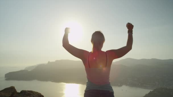 Woman reaches top of the mountain and raises her arms