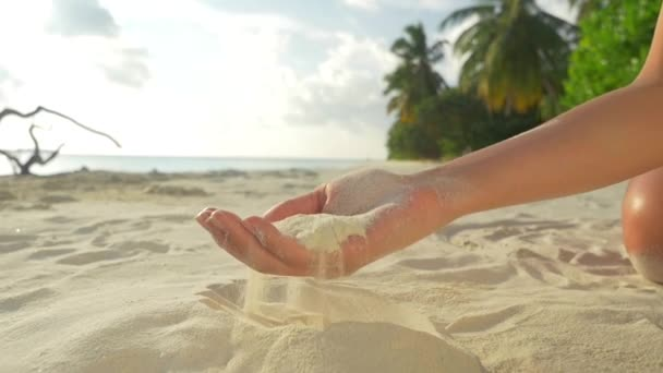 SLOW MOTION: Female scattering white sand at exotic sandy beach
