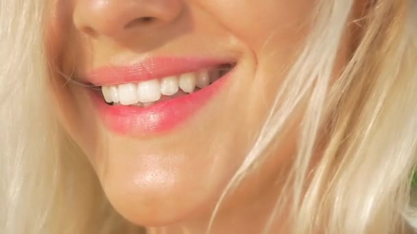 SLOW MOTION CLOSE UP: Beautiful blonde girl smiling