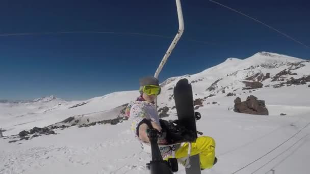 snowboardista jezdí na vleku v horách a fotí se na kameře
