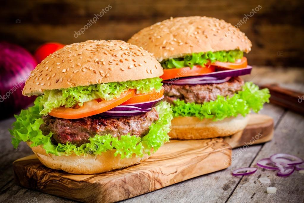 Two homemade burgers with fresh organic lettuce, tomato and red onion