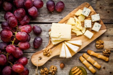 Cheese plate: Emmental, Camembert cheese, blue cheese, bread sticks, walnuts, hazelnuts, honey, grapes on wooden table stock vector