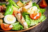 Caesar salad with croutons, cherry tomatoes and grilled chicken