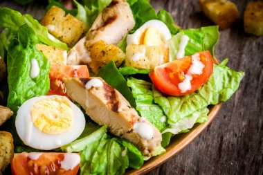 Caesar salad with quail eggs, cherry tomatoes and grilled chicken
