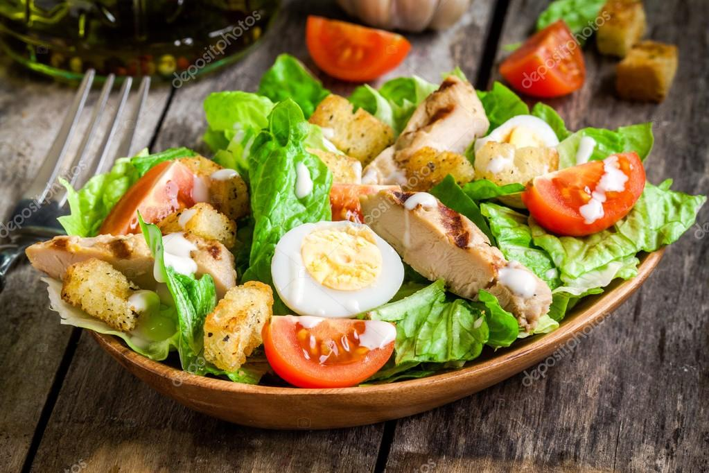 Caesar salad with croutons, quail eggs, cherry tomatoes and grilled chicken in wooden plate