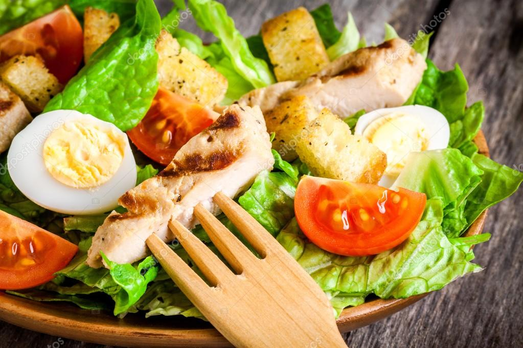 Caesar salad with quail eggs, cherry tomatoes and grilled chicken close up