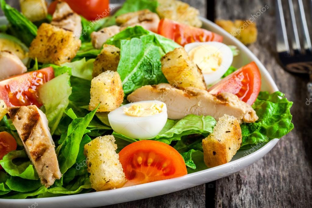 Caesar salad with croutons, quail eggs, cherry tomatoes and grilled chicken close up