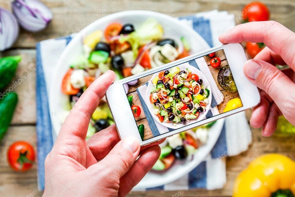 Smartphone taking picture from greek salad