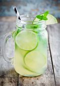 Fotografie homemade lemonade with lime, mint in a mason jar on a wooden table