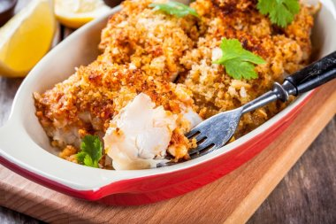 Baked cod fish in breadcrumbs in gratin dish closeup