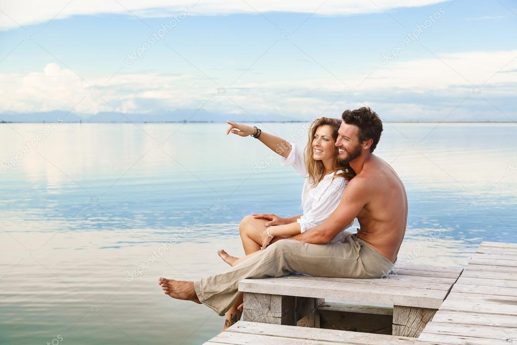 Smiling Couple sitting and pointing to the horizon