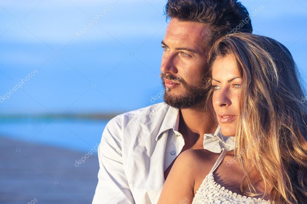 Man embracing his woman from behind on seaside background under