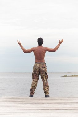 Rear View of Athletic Topless Soldier at the Beach