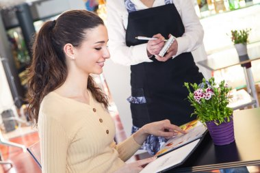 woman ordering to a waitress in a restaurant