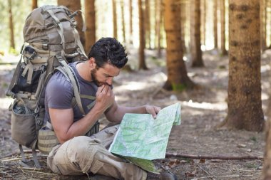 Man with Backpack and map searching directions