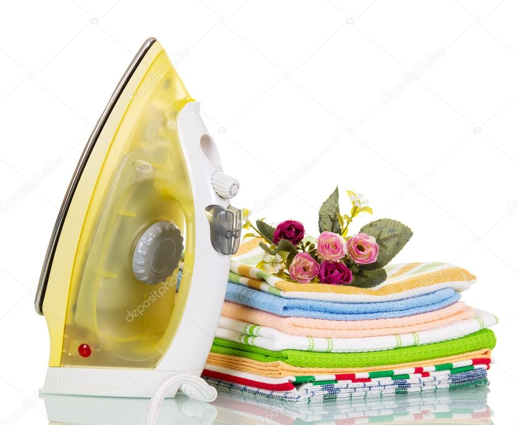 Steam iron and colored cotton towels isolated on white.
