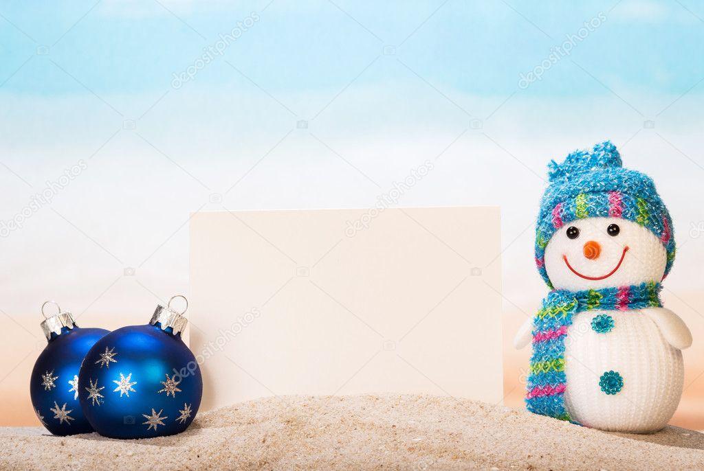 Blank white postcard, snowman , Christmas balls in  sand onseashore.