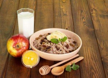 Bowl  oatmeal with raisins and  banana, milk, honey ,apple.
