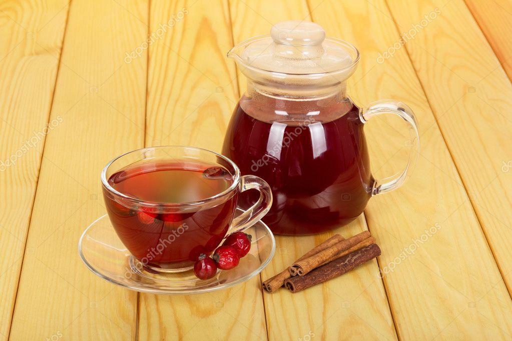 Jug with  drink, cup tea rosehip berries on  light wood.