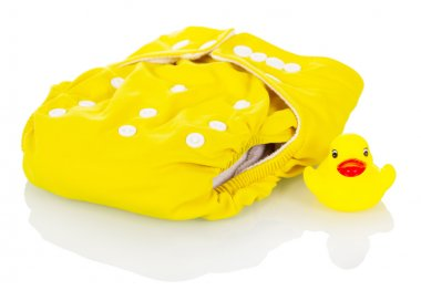 Modern cloth diapers and rubber duck isolated on white.
