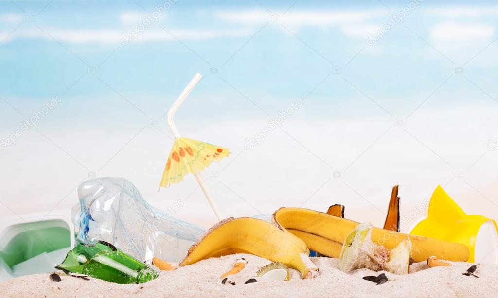 Food and household waste in sand against the blue sea.