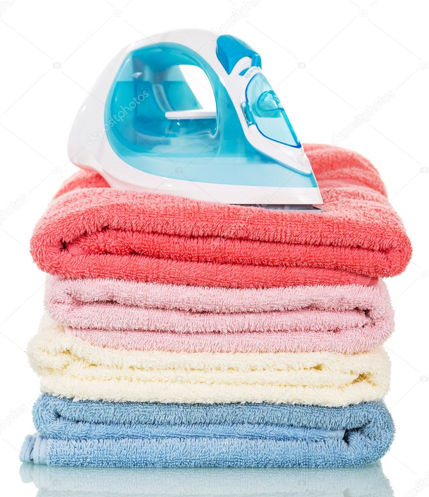 Steam iron and ironing colored towels isolated on white.