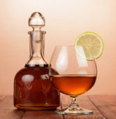 Photo Cognac in bottle and glass with lemon