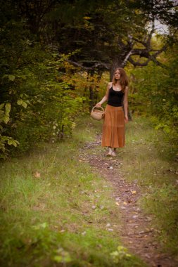 Red-haired young girl with a basket of walks in the woods