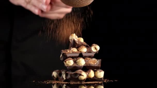 posypte čokoládovou tyčinku kakaovým práškem. hromada tmavé čokolády s ořechy na černém pozadí. koncepce cukrovinek