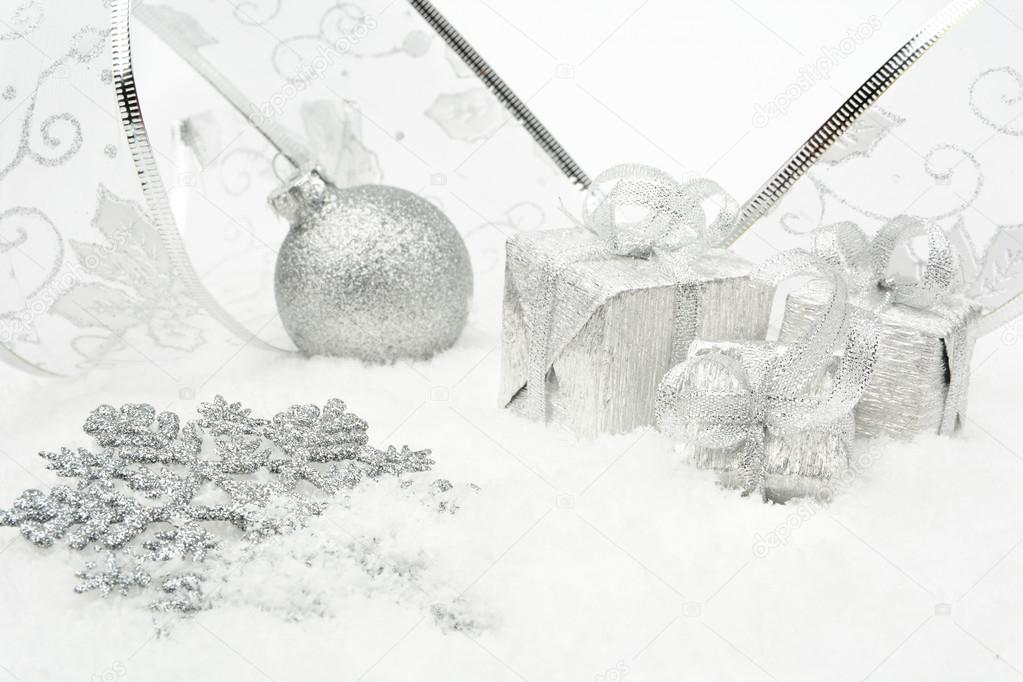 0b233d2564ce4 Decoration of silver christmas baubles and gifts with ribbon on snow on white  background — Photo by dla4