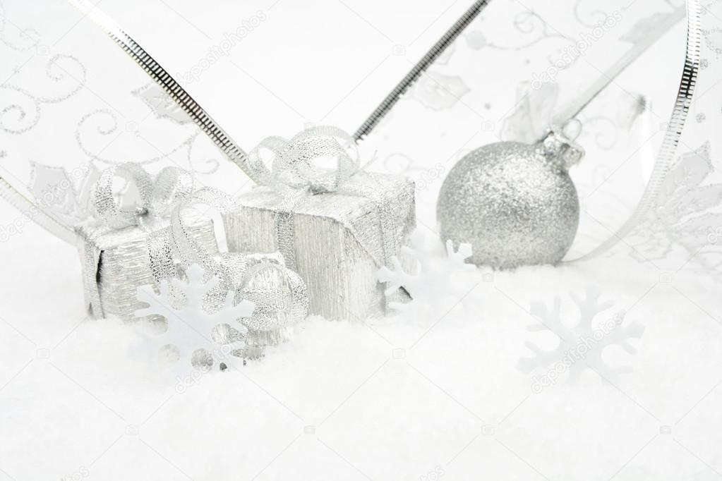 a785be2e278af Decoration of silver christmas baubles and gifts with ribbon on snow on white  background — Photo by ...